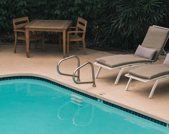Piscine et chaises longues avec de la végétation ainsi qu'une table en bois